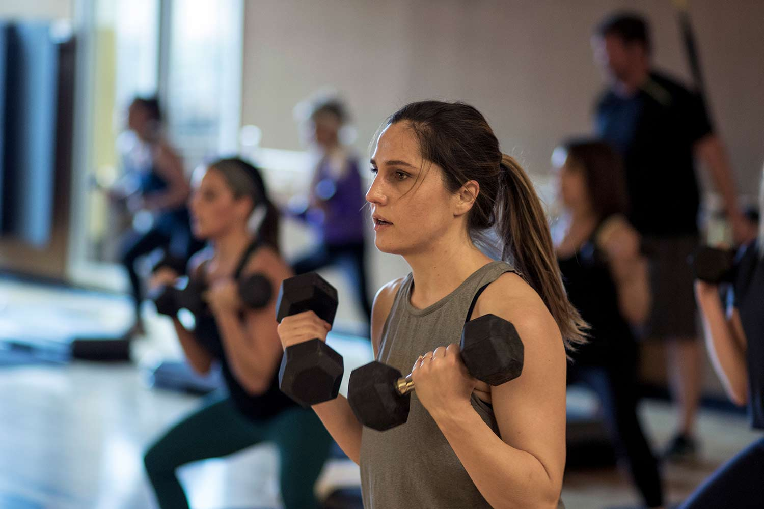Female lifting weights during a HIIT group class.