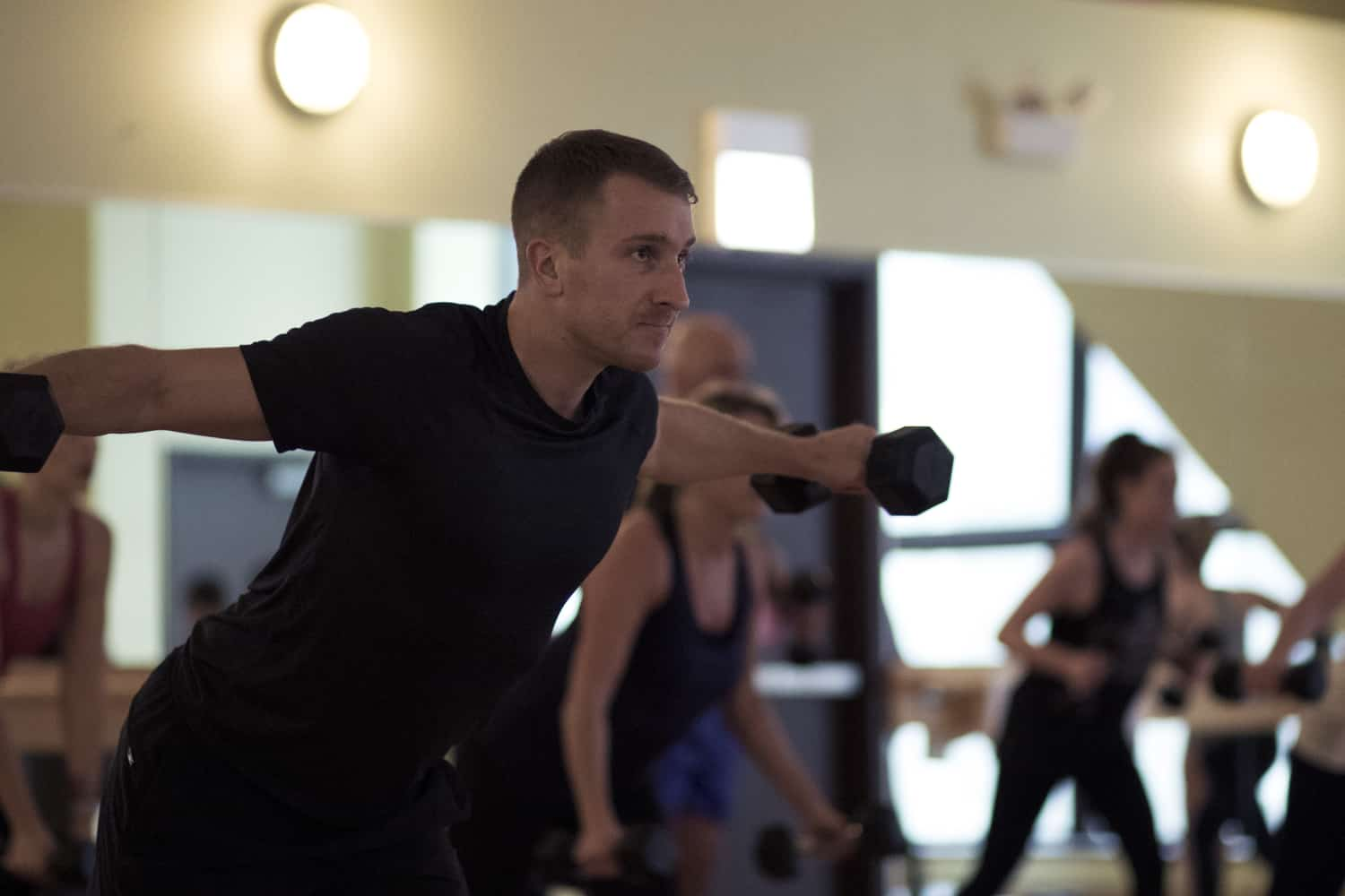 Man doing arm raises during a group fitness class at FFC.
