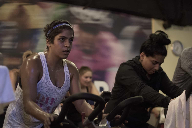 Women working hard in spin class.