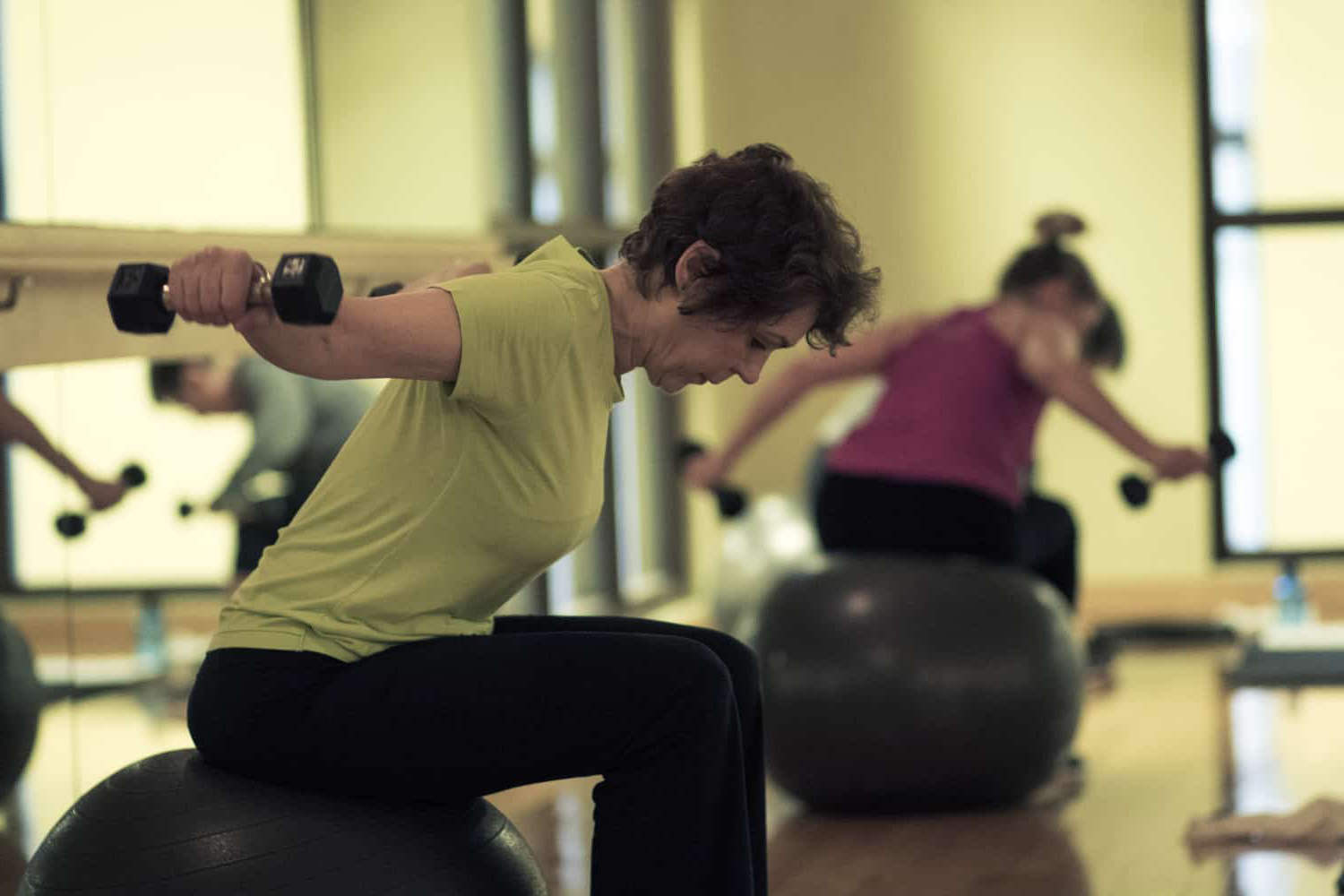 Woman concentrating on lifting weights during Body360.