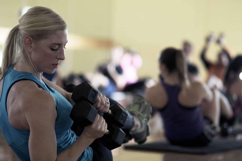 Motiv8 class member lifting weights.