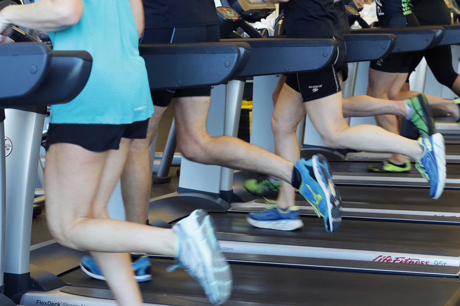Group of people running on treadmills.