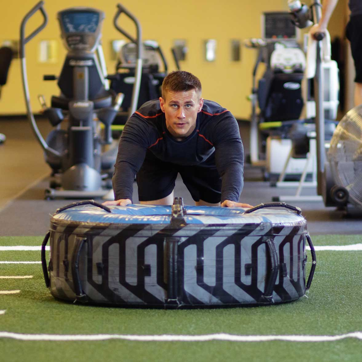 Man pushing a tire across the turf in the Performance Training Center.