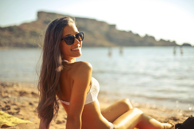 Tan female smiling on the beach.