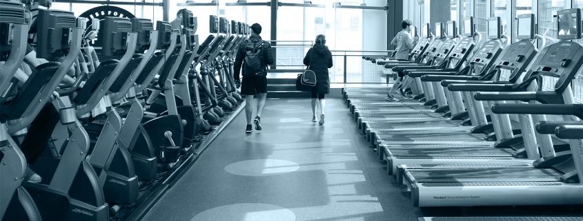 FFC West Loop members walking together between fitness machines.
