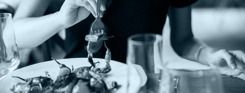 Woman eating pasta at a nice restaurant.