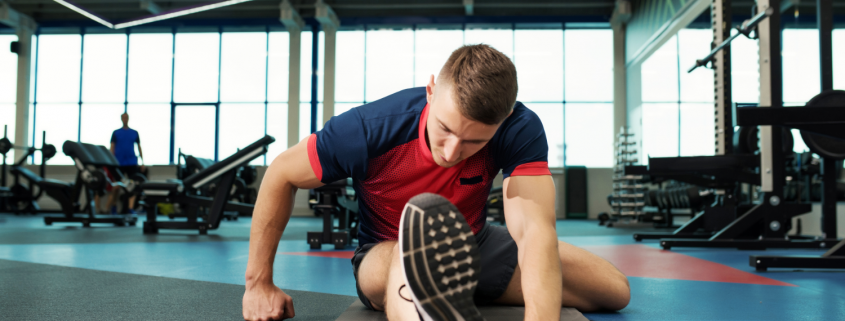 Man stretching on gym floor