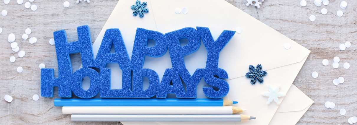 Happy Holidays graphic on a table with pencils and snowflakes