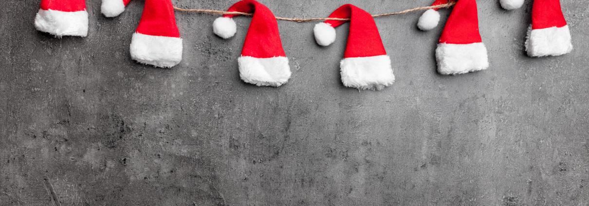 Santa hats on a string against gray wall