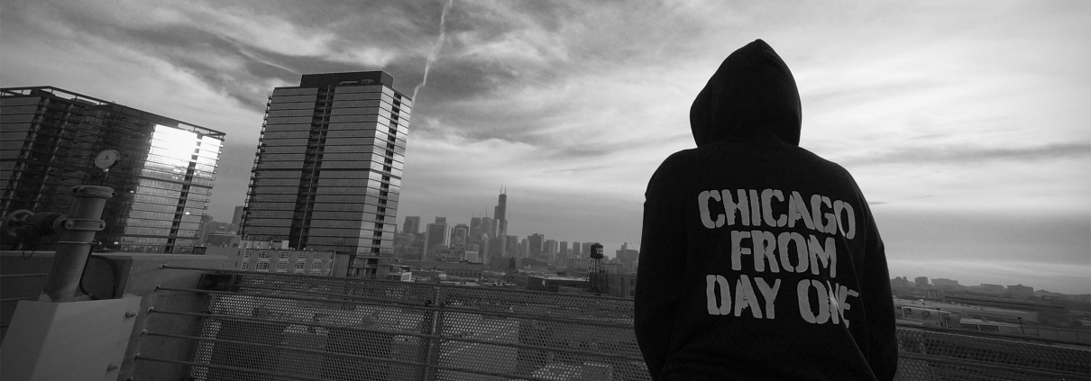 Image of a man standing in front of the Chicago skyline wearing an FFC 'Chicago From Day One' campaign sweatshirt.