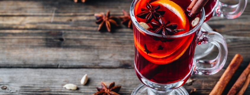 Mulled red wine with spices and orange in glass on a wooden rustic background. Homemade Christmas drink.