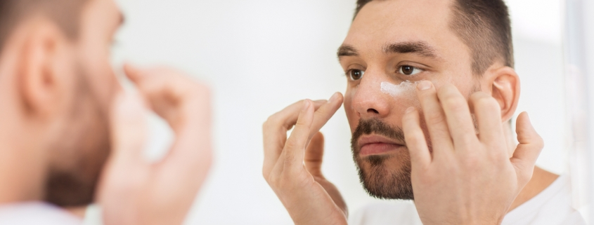 young man applying moisturizer to face and looking to mirror at home bathroom
