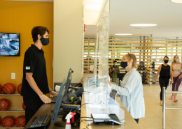 Man and woman at fitness center check in desk wearing face masks