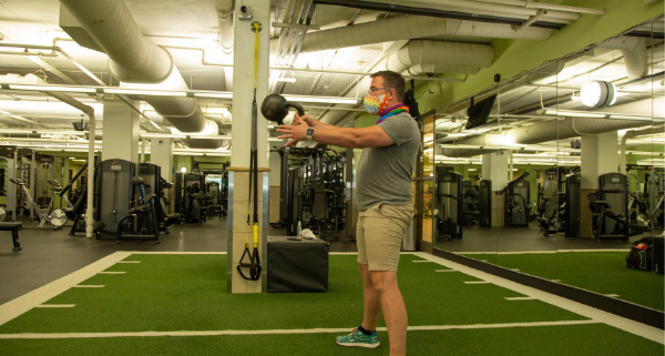 Man wearing a mask and swinging a kettlebell in the gym.