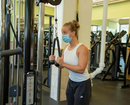 member wearing a mask exercising