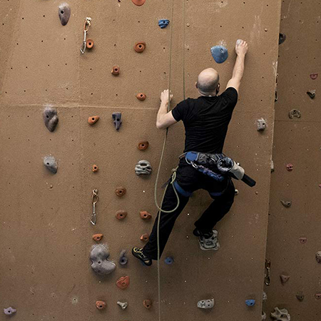 Man climbing up a climbing wall.