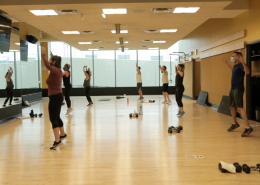 Photo of people with arms raised in a group fitness class