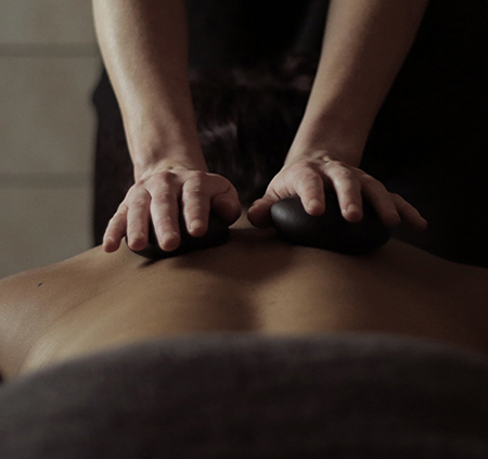 Client receiving a stone massage.
