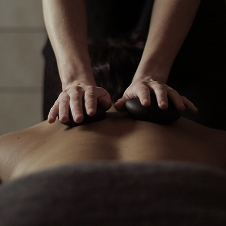 Client receiving a stone massage.
