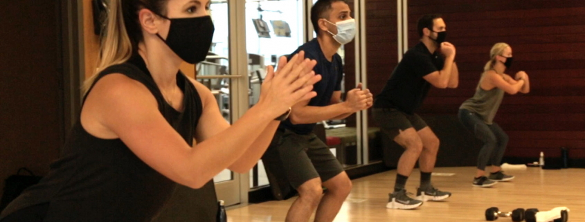 Photo of a group fitness class in process with masks and social distancing