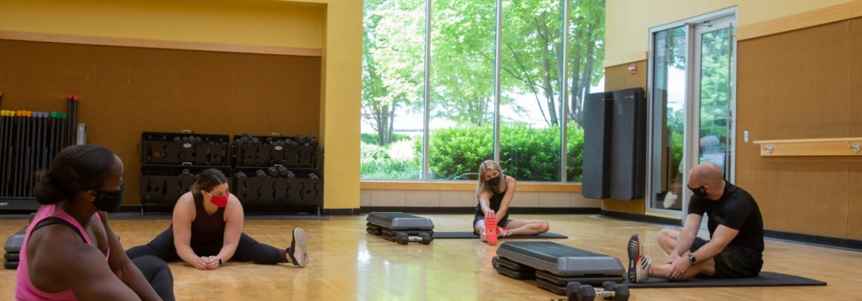 Photo of 4 friends stretching in a group fitness studio