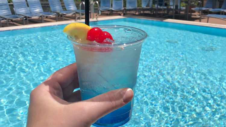 Hand holding a drink near a pool in the summer