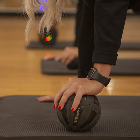 Woman Holding the Hyperice vibrating ball while in plank position