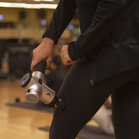 Photo of a woman using the hypervolt percussion recovery device