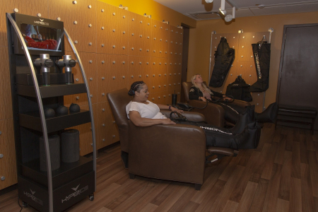 Photo fo the FFC Gold Coast recovery lounge with two women seated in compression boots