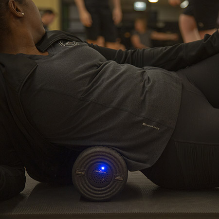 Woman using the Viper vibration foam roller on her back