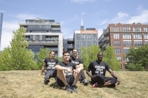 Group of FFC employees seated in grass with Willis Tower in background