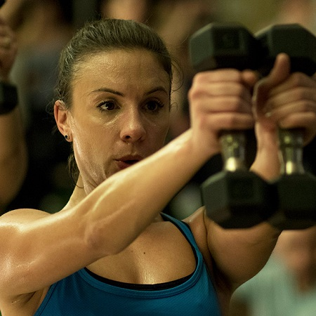 Photo of woman sweating with weights in a class