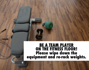 A workout bench covered in sweat with dumbbells and other equipment laying near it.