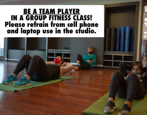 Photo of a woman texting on her phone in the back of a group fitness class.