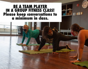 Photo of two women talking distractedly during a group fitness class.